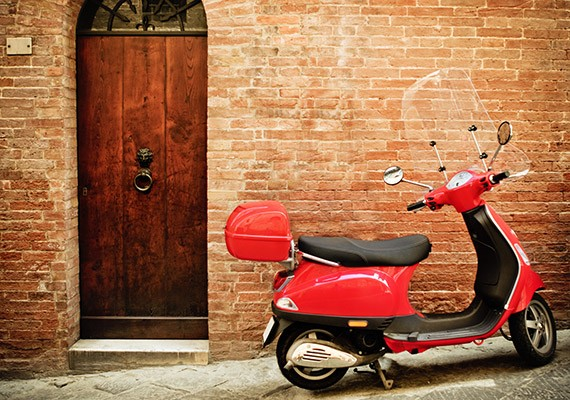 Vintage image of red scooter on the street of Italy